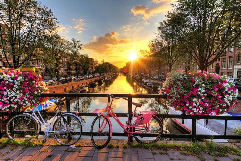 Gün batımında kanal ve 2 bisiklet Amsterdam Hollanda